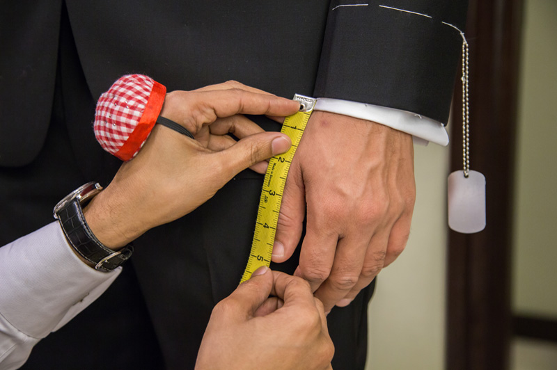 tailor is measuring for a tuxedo being made